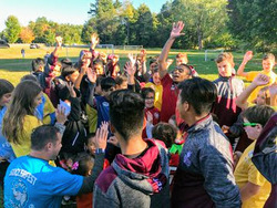 Students cheer after huddle during soccer program